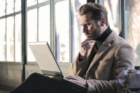 Mann starrt fragend auf Laptop